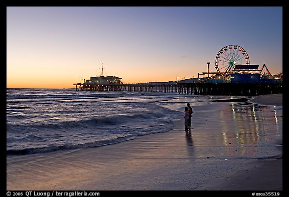 Couple reflected in wet sand at sunset, with pier and Ferris Wheel behind. Santa Monica, Los Angeles, California, USA