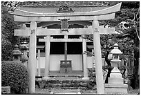Tori gate at the entrance of a shrine inner grounds. The act of passing through purifies the soul.. Kyoto, Japan ( black and white)