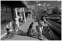Woman and kids with mountain bikes on downtown Banff sidewalk. Banff National Park, Canadian Rockies, Alberta, Canada (black and white)