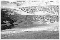 Distant view of snowcoaches parked at the base of the lower icefall on the Athabasca Glacier. Jasper National Park, Canadian Rockies, Alberta, Canada ( black and white)