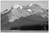Canoe dwarfed by the Mt Charlton and Mt Unwin surrounding Maligne Lake. Jasper National Park, Canadian Rockies, Alberta, Canada ( black and white)