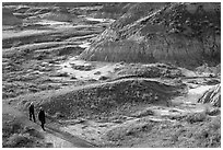 Hikers amongst badlands, morning, Dinosaur Provincial Park. Alberta, Canada (black and white)