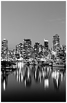 Fishing boats and skyline light reflected at night. Vancouver, British Columbia, Canada (black and white)