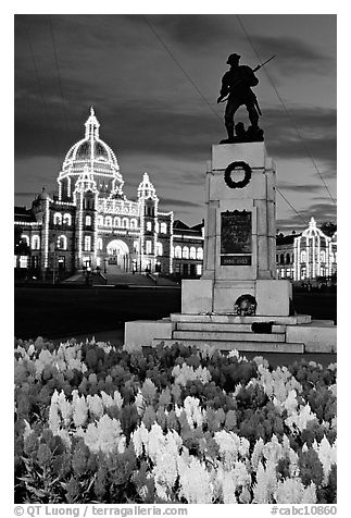 Flowers, memorial statue and illuminated parliament building at night. Victoria, British Columbia, Canada (black and white)