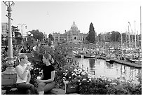 Women drinking coffee at the Inner Harbour, sunset. Victoria, British Columbia, Canada ( black and white)