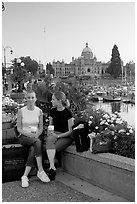 Women with shopping bags and coffee cups at the Inner Harbour, sunset. Victoria, British Columbia, Canada ( black and white)