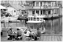 People eating fish and chips on deck,  Fisherman's wharf. Victoria, British Columbia, Canada ( black and white)