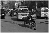 Tricycle and taxi on street. Beijing, China (black and white)