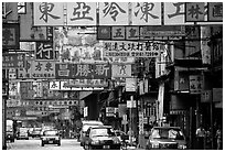 Taxicabs in a street filled up with signs in Chinese, Kowloon. Hong-Kong, China ( black and white)