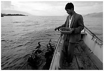 Cormorant fisherman feeds small fish to his birds as a prize for catching large fish. Dali, Yunnan, China (black and white)