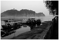 Boats along the river with cliffs in the background. Leshan, Sichuan, China ( black and white)