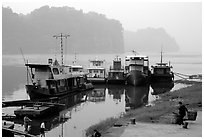 Boats along the river with misty cliffs in the background. Leshan, Sichuan, China ( black and white)