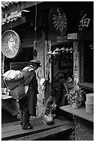 Naxi woman offers eggs for sale to local residents. Lijiang, Yunnan, China (black and white)