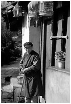 Naxi woman at the door of her wooden house. Lijiang, Yunnan, China (black and white)
