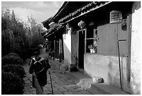 Naxi woman sweeps the floor at the door of her wooden house. Lijiang, Yunnan, China ( black and white)