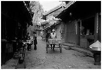 Early morning activity in a cobblestone street. Lijiang, Yunnan, China ( black and white)