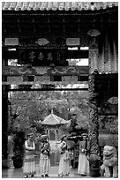 Women in Naxi dress standing in an archway. Lijiang, Yunnan, China (black and white)