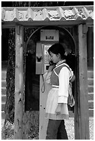 Woman in Naxi dress in a telephone booth. Lijiang, Yunnan, China (black and white)