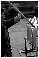 Woman Pilgrim lighting a large incense stick, Wannian Si. Emei Shan, Sichuan, China ( black and white)