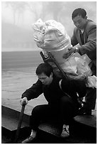 Porter getting helped to shoulder a heavy load on a back frame. Emei Shan, Sichuan, China ( black and white)