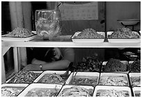 Vendor taking a nap at a food stall.. Chengdu, Sichuan, China (black and white)