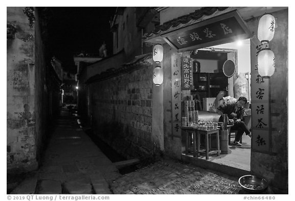 Shopkeeper and alley at night. Hongcun Village, Anhui, China (black and white)