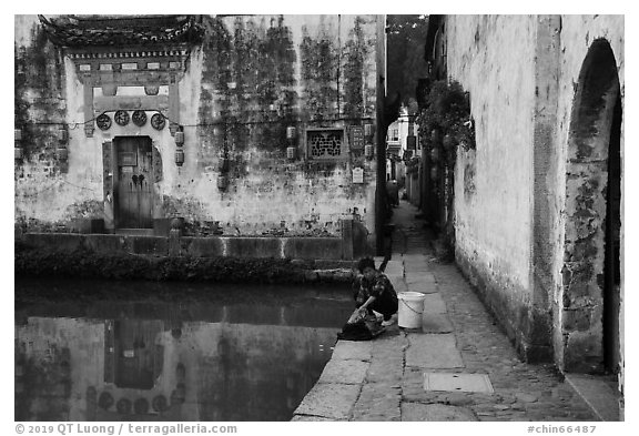 Woman washes laundry in Moon Pond. Hongcun Village, Anhui, China (black and white)