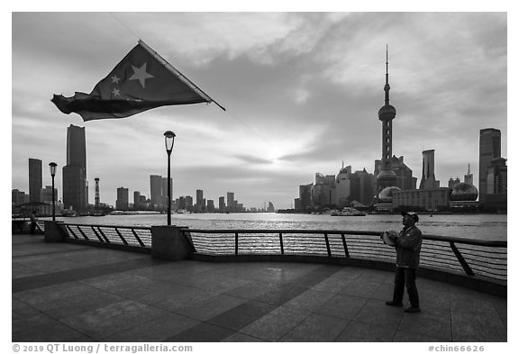Man flying kite with Chinese flag attached on line, the Bund. Shanghai, China (black and white)