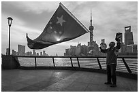 Man saluting Chinese flag and skyline, the Bund. Shanghai, China ( black and white)