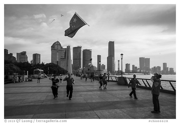 Joggers salute Chinese flag flown on kite line, the Bund. Shanghai, China (black and white)