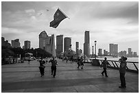 Joggers salute Chinese flag flown on kite line, the Bund. Shanghai, China ( black and white)