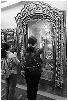 Women pray to deity, Guandu Temple. Taipei, Taiwan ( black and white)