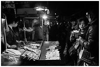 Sampling snacks at Shilin Night Market. Taipei, Taiwan ( black and white)