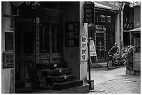 Man on bicycle amidst old houses in alley. Lukang, Taiwan (black and white)