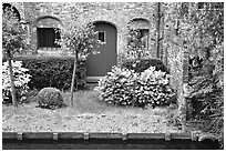 Small garden and brick house by the canal. Bruges, Belgium (black and white)