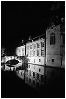 Houses and bridge reflected in canal at night. Bruges, Belgium (black and white)