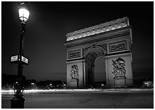 Street lamp and Etoile triumphal arch at night. Paris, France ( black and white)