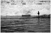 Man standing at water level fishing in the Seine River. Paris, France ( black and white)