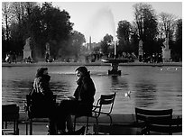 Couple sitting by basin in Tuileries Gardens. Paris, France (black and white)