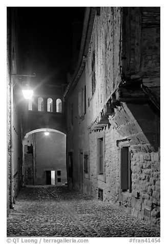 Cobblestone street by night inside medieval city. Carcassonne, France (black and white)