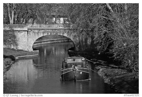 Tranquil scene with barge, bridge, and trees, Canal du Midi. Carcassonne, France (black and white)