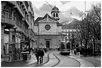 Street with people walking, tramway and church. Grenoble, France ( black and white)
