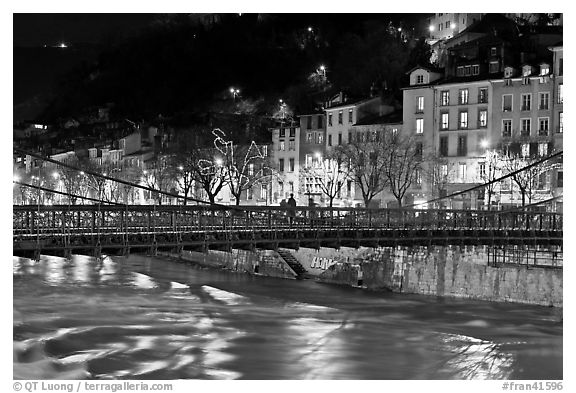 Suspension bridge at night with Christmas lights reflected in river. Grenoble, France (black and white)