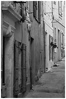 Painted facades in narrow street. Arles, Provence, France ( black and white)