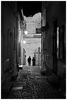 Narrow cobblestone passageway at night next to arena. Arles, Provence, France ( black and white)