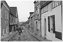 Pedestrian with umbrella in narrow street, Provins. France ( black and white)