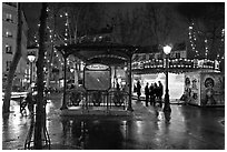 Square with subway entrance and carousel by night. Paris, France (black and white)
