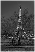 Bicyclists and Eiffel tower at night. Paris, France (black and white)