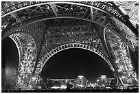Palais de Chaillot seen through the base of Eiffel Tower by night. Paris, France ( black and white)