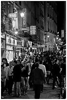 Busy pedestrian street at night. Quartier Latin, Paris, France (black and white)